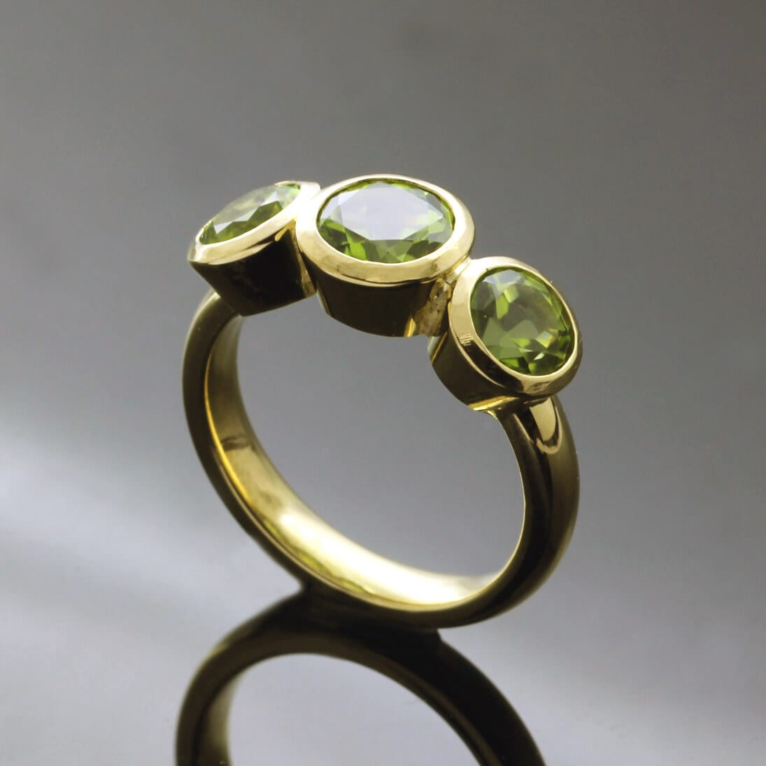 Handmade Bespoke Peridot Trilogy ring in Yellow Gold