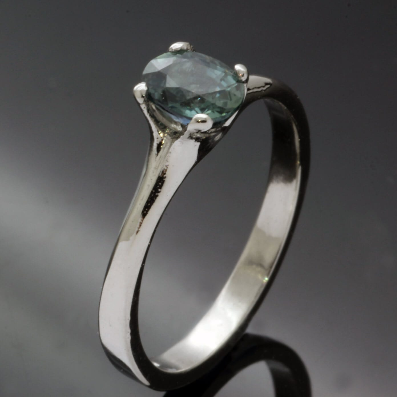 Modern and unique Platinum Teal Sapphire engagement ring