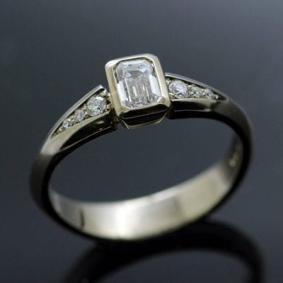 Emerald cut Diamond with twin shoulders of Diamonds set in White Gold modern engagement ring