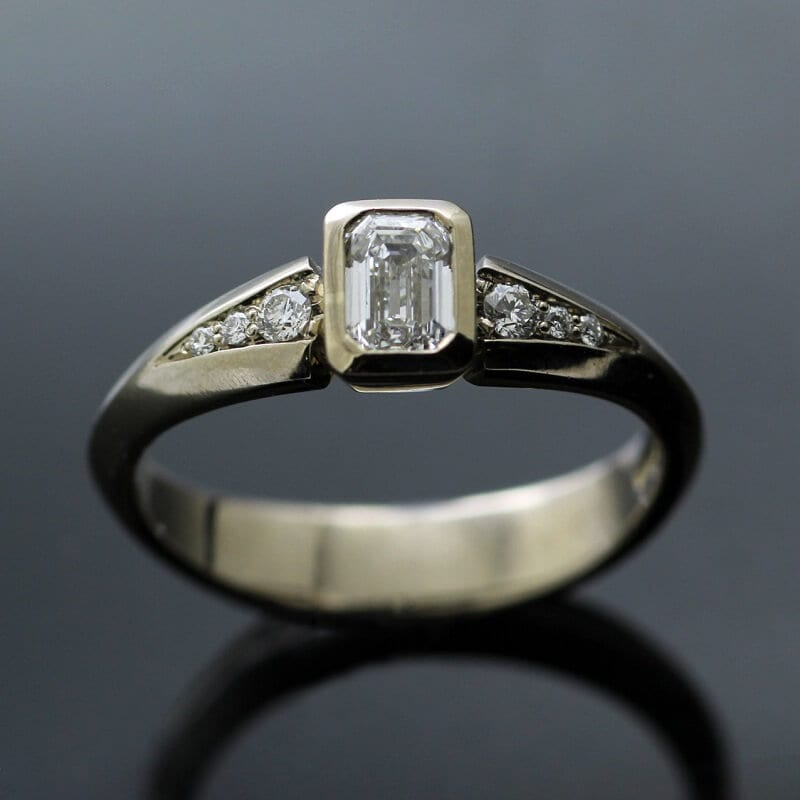 White Gold and Emerald cut engagement ring with twin shoulders of pave set Diamonds
