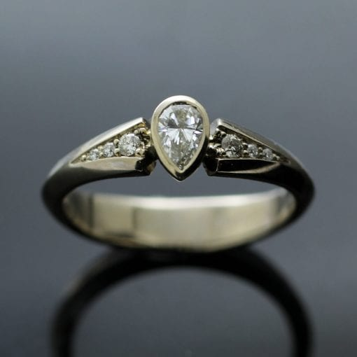 Pear Cut Diamond and white Gold engagement ring with pave set Diamond shoulders