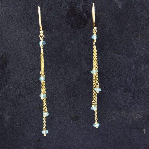 gold chain earrings on slate